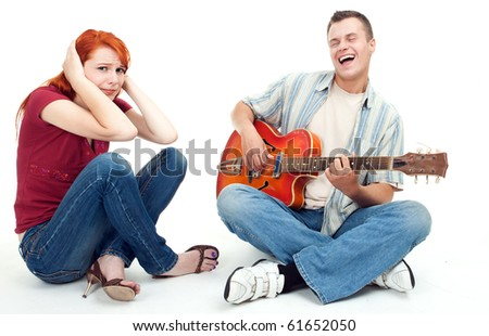 couple with electric guitar - man playing and singing, woman listening with horror - stock photo