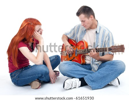 couple with electric guitar - man playing and woman listening with pleasure - stock photo