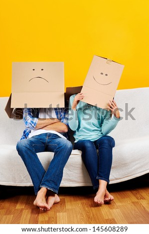 couple with empty box on head moving into new home fun game - stock photo
