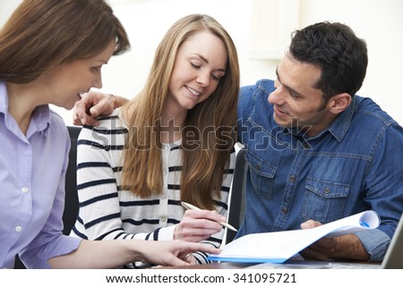 Couple With Financial Advisor Signing Document In Office - stock photo
