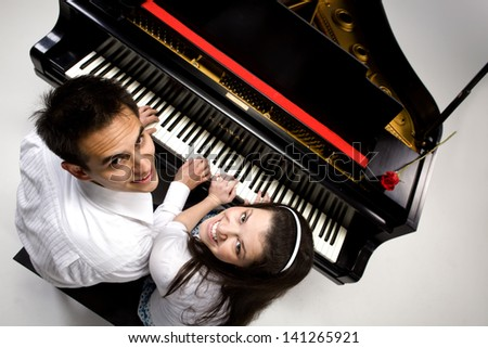 Couple with Grand piano 5 sitting at piano bench with red rose. - stock photo