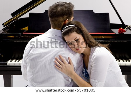 Couple with Grand piano 3 sitting at piano bench with red rose - stock photo