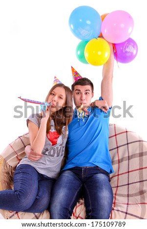 Couple with hats and balloons sitting on the couch isolated - stock photo