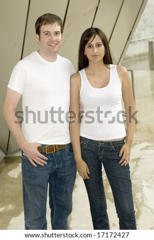 Couple with jeans and white tops posing outside - stock photo