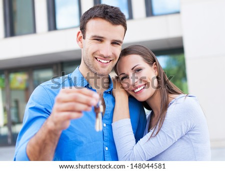 Couple with keys to new home - stock photo