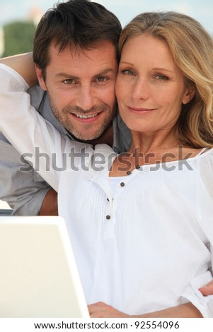 Couple with laptop in garden