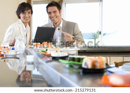 Couple with laptop in sushi bar, smiling, portrait - stock photo