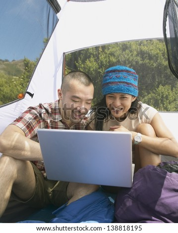Couple with laptop in tent - stock photo