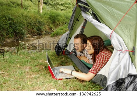 Couple with laptop lying in a tent - camping serie - stock photo