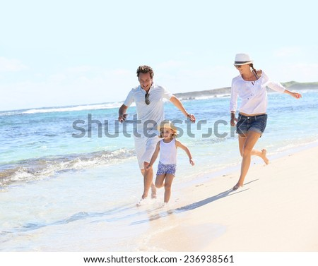 Couple with little girl running on Caribbean beach - stock photo