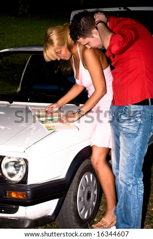 couple with map looking for direction infront their car - stock photo