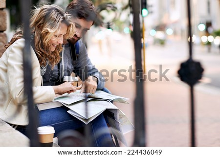 couple with map looking for directions in new city on vacation - stock photo