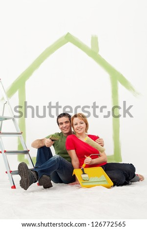 Couple with painting utensils resting in their home - redecorating concept - stock photo