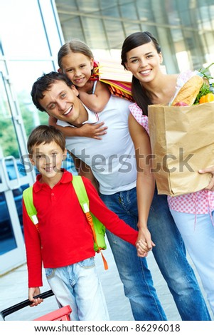 Couple with paperbags and their two children after shopping - stock photo