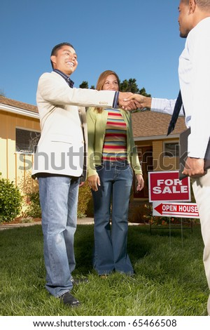 Couple with realtor at open house - stock photo