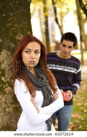 Couple with relationship problem, she is angry with him, but he have a present to make her happy (selective focus with shallow DOF) - stock photo