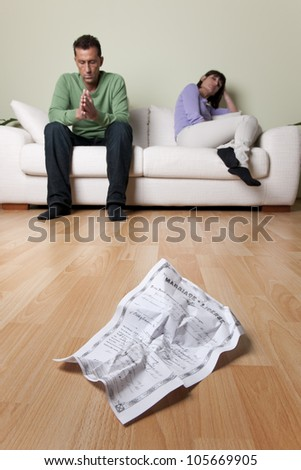 Couple with relationship problems, creased wedding certificate on foreground - stock photo