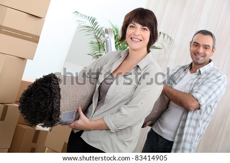 Couple with rolled up carpet surrounded by boxes - stock photo