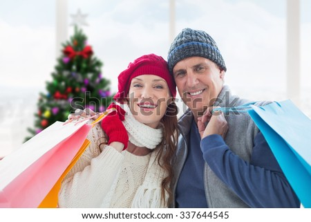 Couple with shopping bags against home with christmas tree