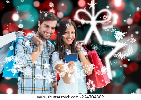 Couple with shopping bags and credit card against blurred christmas background - stock photo