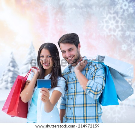 Couple with shopping bags and credit card against snowy landscape with fir trees - stock photo