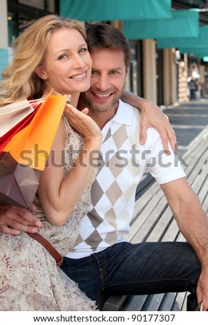 Couple with shopping bags outside boutiques - stock photo