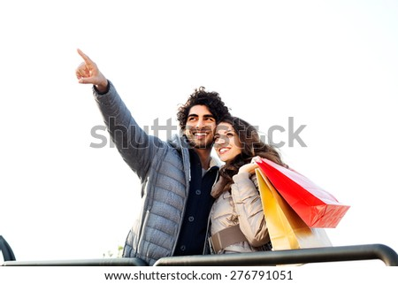 Couple with Shopping Bags Pointing into Distance - stock photo