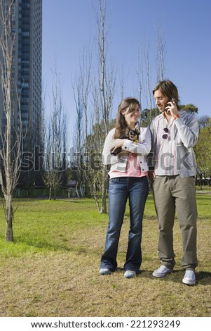 Couple with small dog in park - stock photo