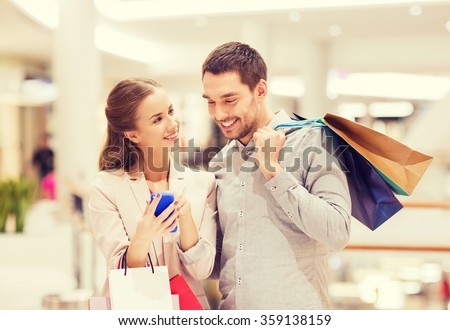 couple with smartphone and shopping bags in mall - stock photo