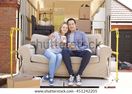 Couple With Sofa On Tail Lift Of Removal Truck Moving Home - stock photo