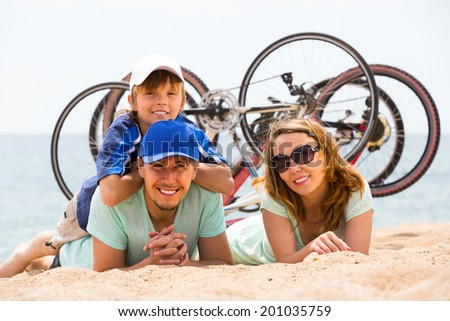 Couple with son lying on sand with bicycles at seashore  - stock photo