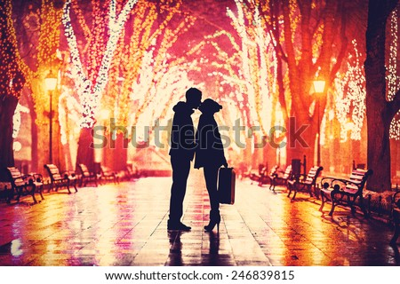 Couple with suitcase kissing at night alley. - stock photo