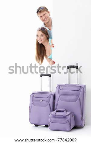Couple with suitcases and billboards on a white background - stock photo