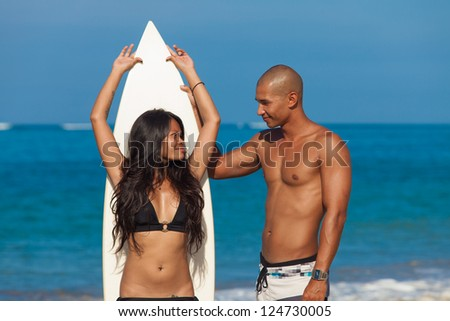couple with surfboard on beach - stock photo
