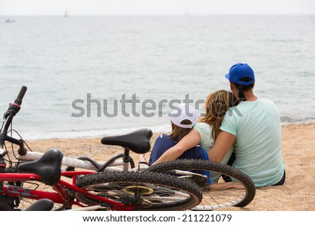 Couple with teenager son with cycles behind in vacation at seaside - stock photo