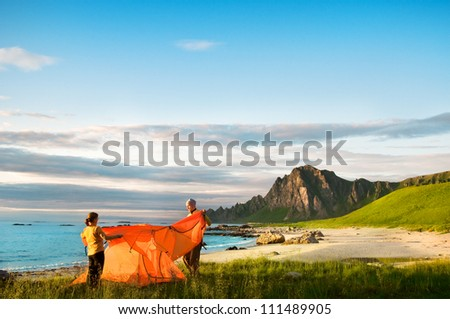 couple with tent near seaside - stock photo