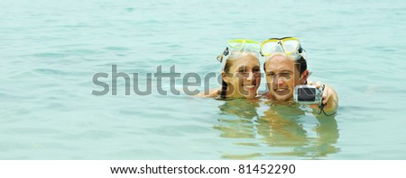 Couple with the masks making photo of themselves in the sea - stock photo