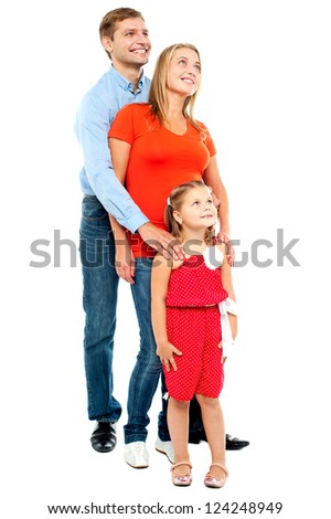 Couple with their girl child looking upwards. Family of three - stock photo