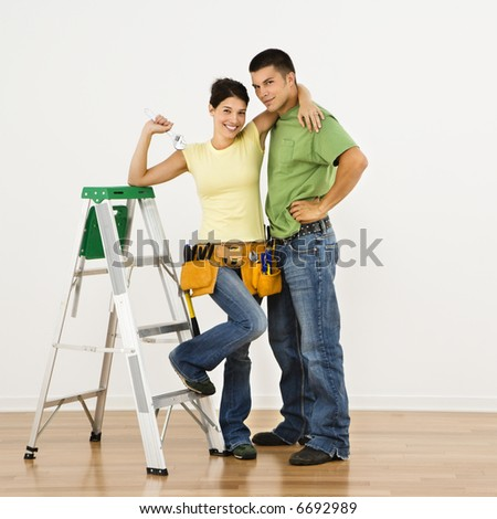 Couple with tools and ladder standing in home smiling. - stock photo