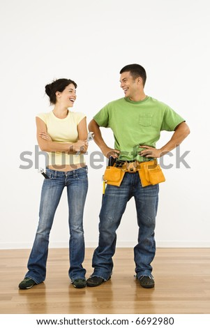 Couple with tools standing and smiling in home. - stock photo
