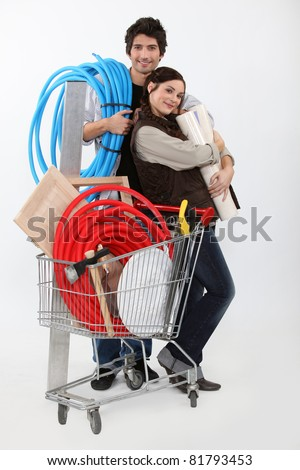 Couple with trolley full of supplies - stock photo