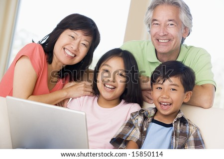Couple with two young children in living room with laptop smiling - stock photo