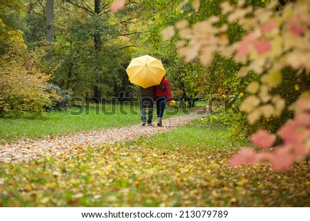 Couple with umbrella during autumn walk in the forest - stock photo