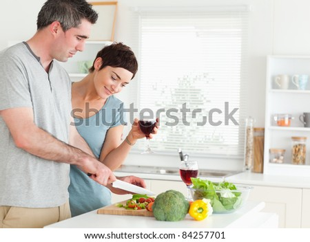 Couple with wine and vegetables in a kitchen