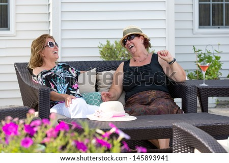 Couple women having happy conversations outside at the patio. - stock photo
