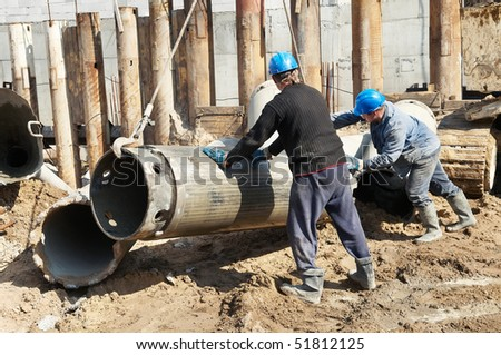 couple workers installing a tube metal form for piling with continuous concrete casting - stock photo