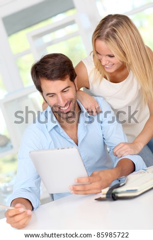 Couple working at home with electronic tablet
