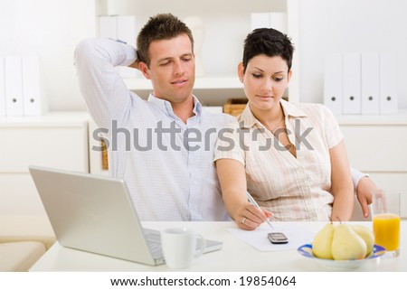 Couple working on laptop computer at home office. - stock photo