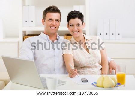 Couple working on laptop computer at home office, smiling. - stock photo