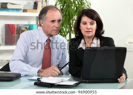 couple working together on laptop - stock photo
